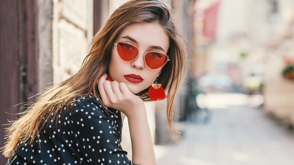 A woman wearing red sunglasses and earrings