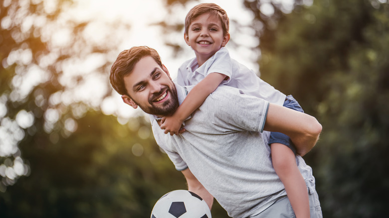 Father and child playing soccer