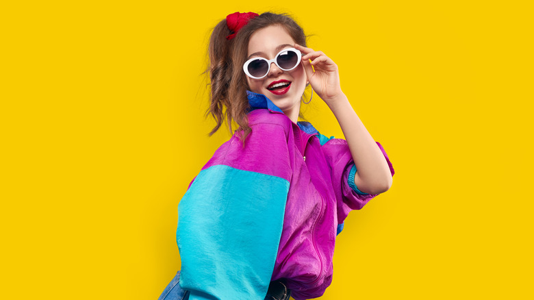 Woman posing, wearing multi-color track jacket and white sunglasses