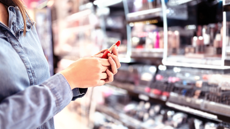 A person selecting lipstick from a drugstore aisle