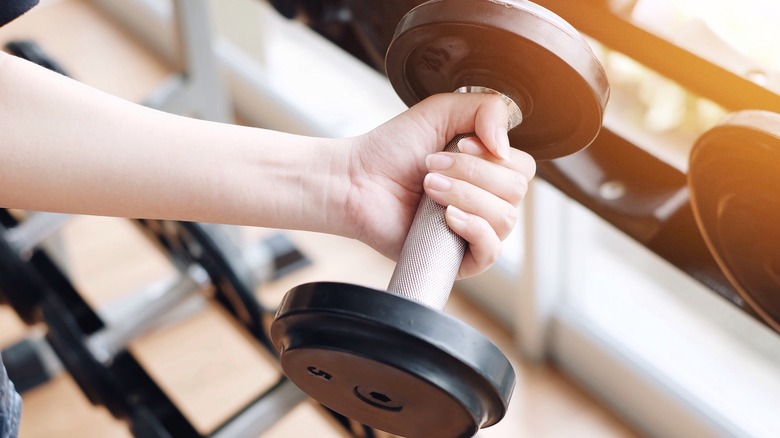 Woman's hand lifting dumbbell weight