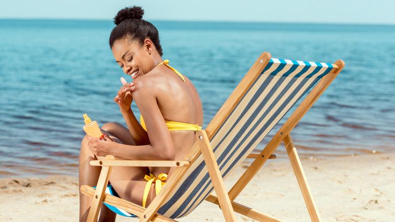 Black woman applying sunscreen