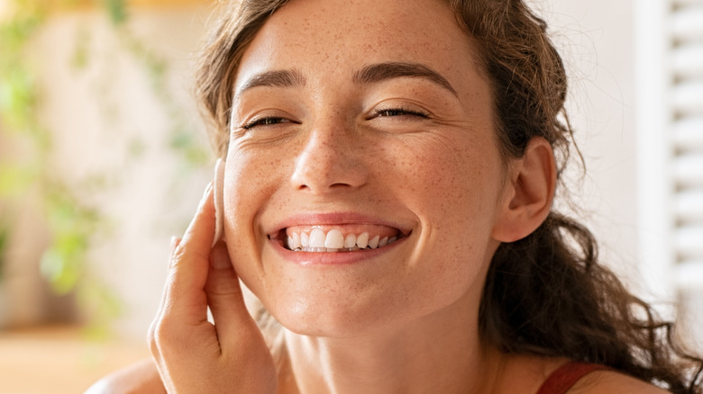Woman with curly hair smiling while washing her face