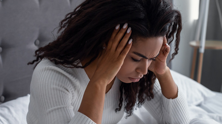 woman in bed with headache from hangover