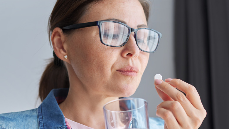 Woman wearing glasses holding a cup of water and an aspirin