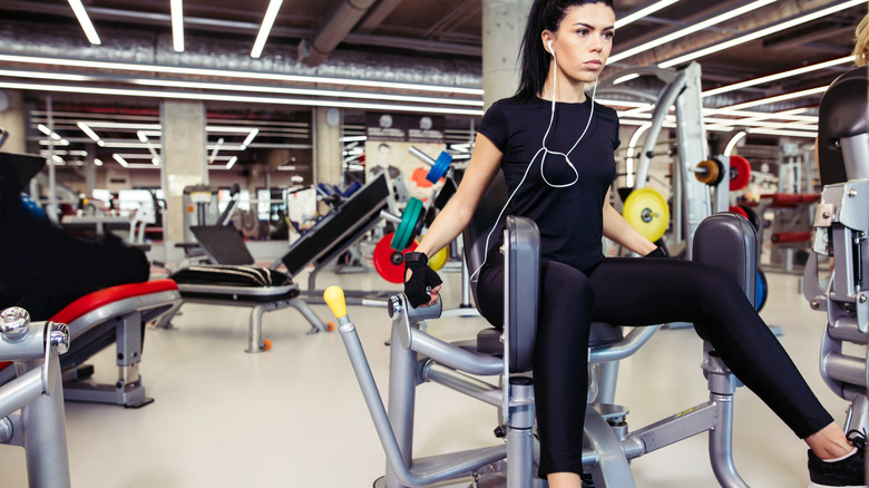 Woman using abduction machine in gym