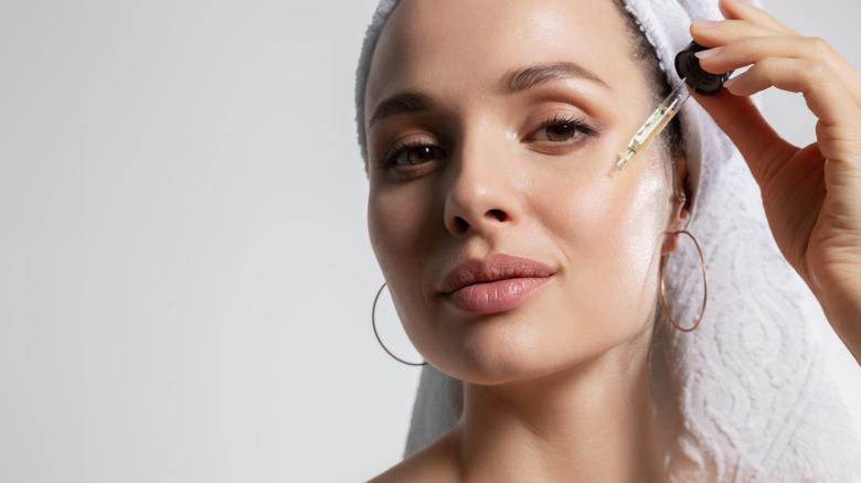 Woman applying face serum to skin