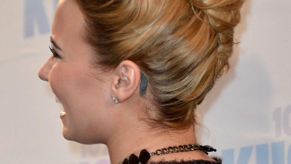 Demi Lovato desviando o olhar com sua tatuagem de pena visível