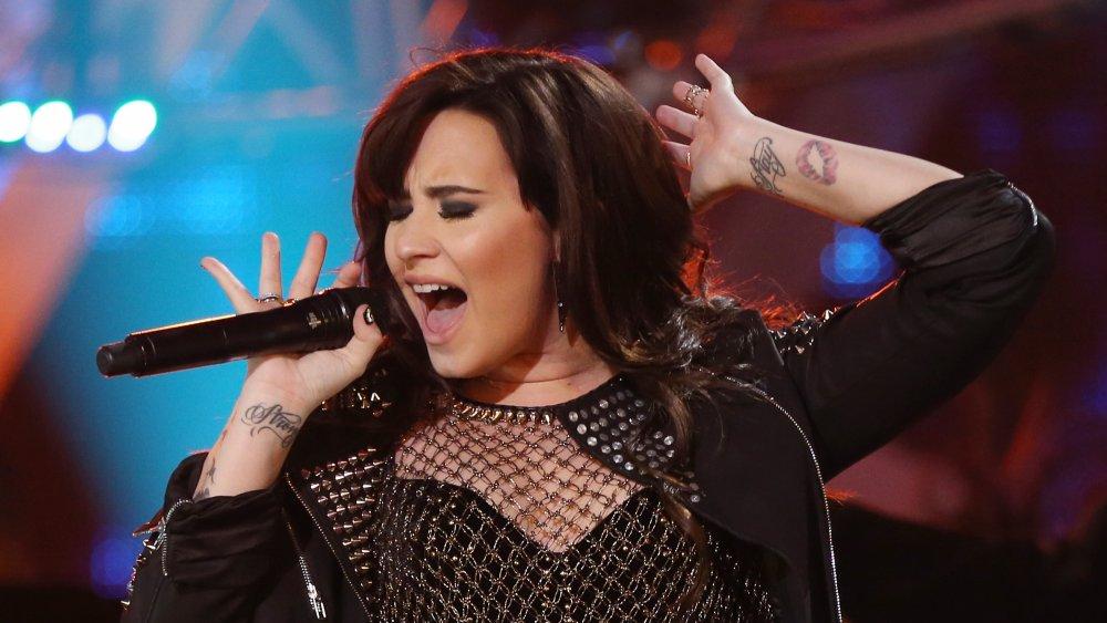 """Demi Lovato se apresentando em 2012 com suas tatuagens """"fique forte"""" visíveis"""