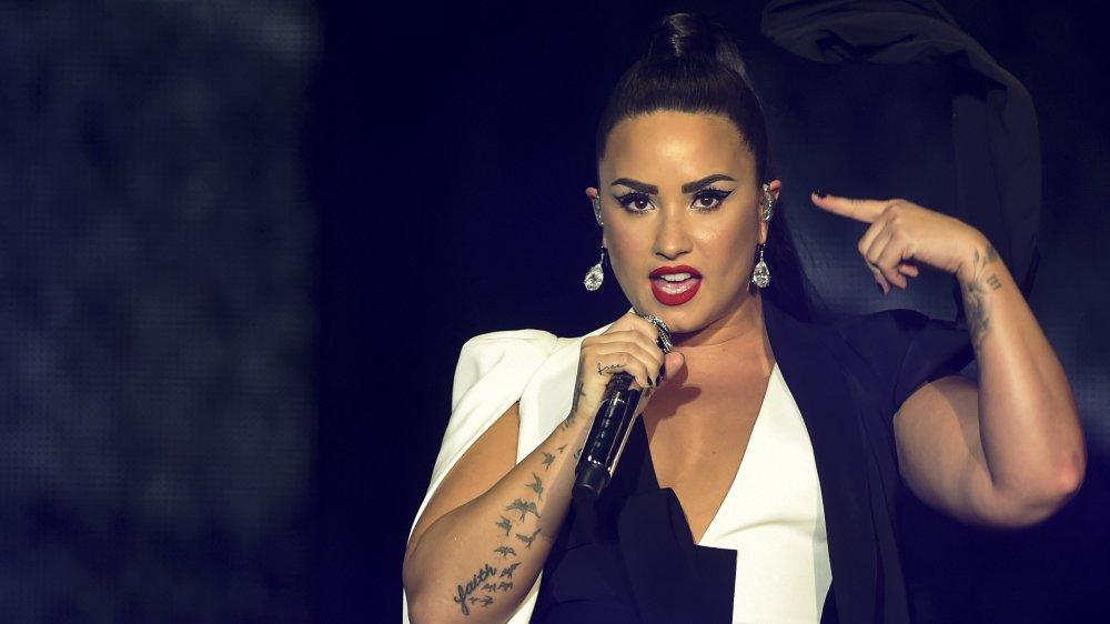 Demi Lovato se apresentando em 2018 com sua tatuagem de pássaro visível