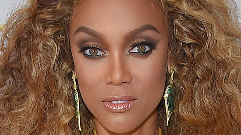 Tyra Banks with hair down and long earrings
