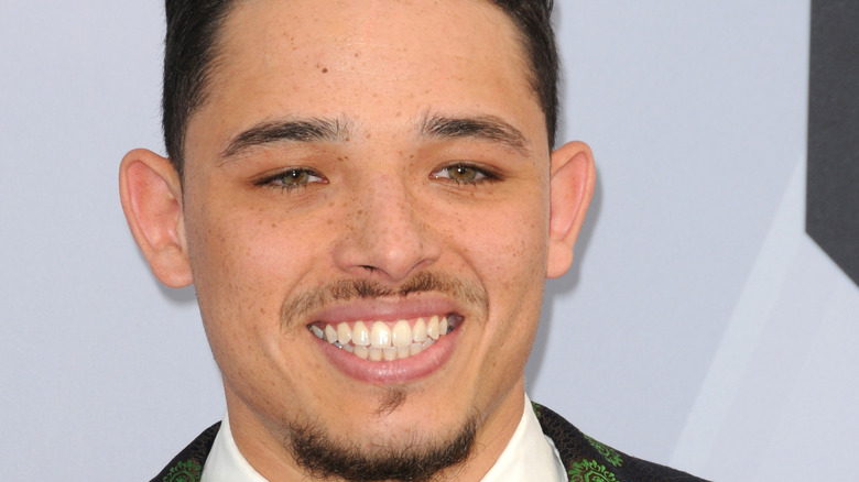 Anthony Ramos smiling in suit