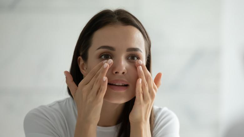 A woman dabbing underneath her eyes