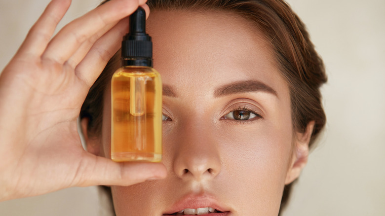 A woman holding serum in front of her face