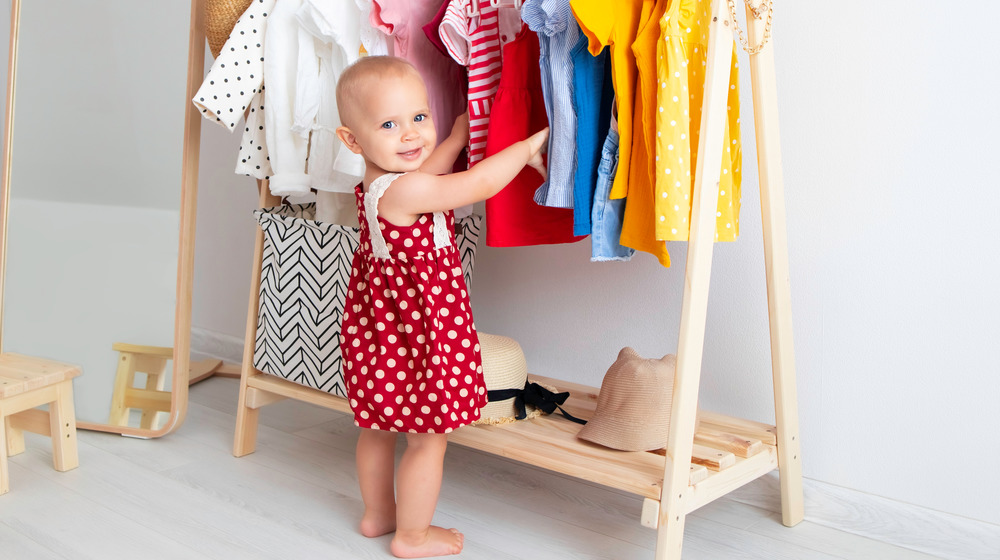 Baby standing by clothes
