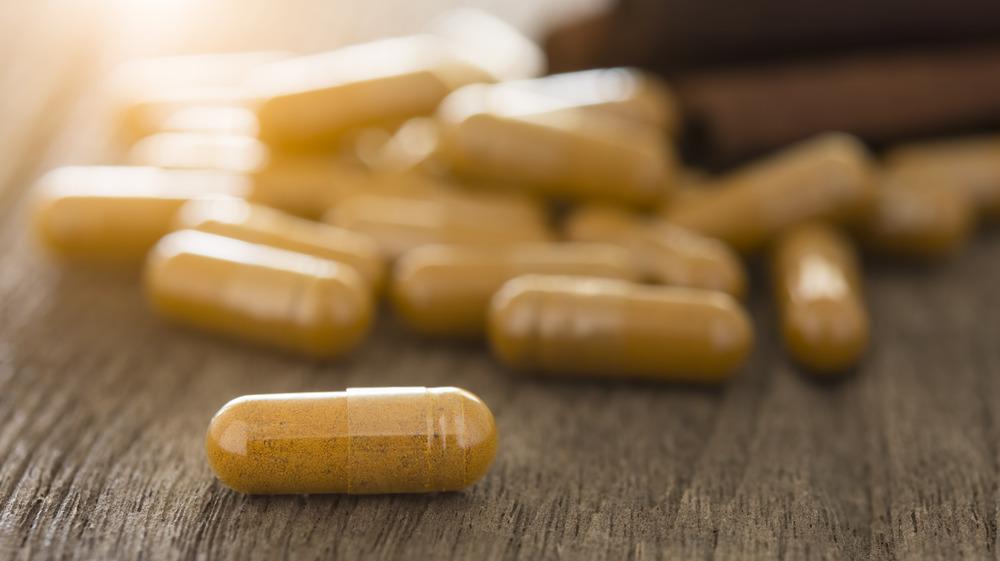 Cinnamon pills on wooden table