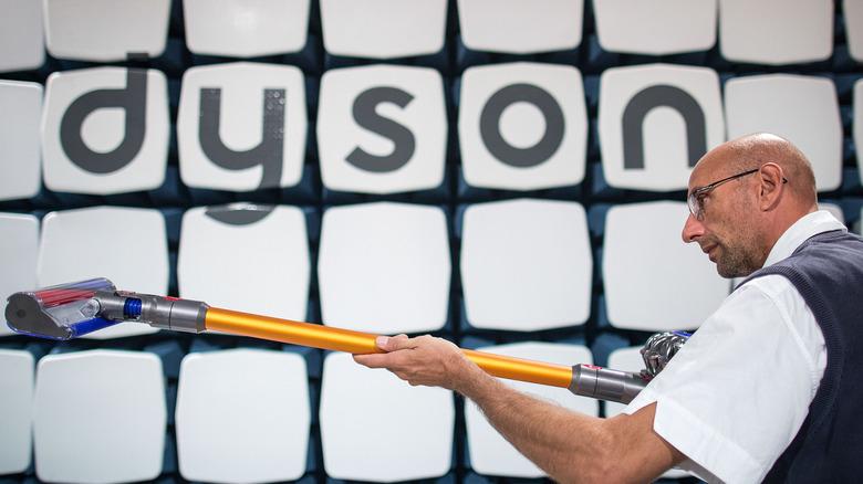 Man holding a Dyson vacuum