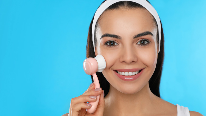 Woman using facial cleansing brush