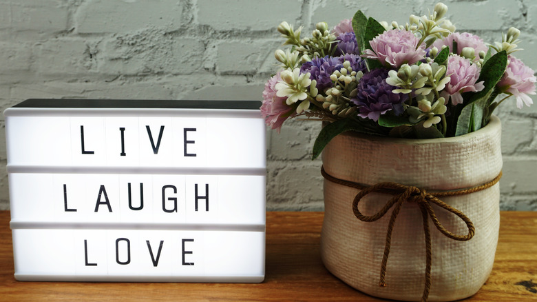 'Live Laugh Love' sign next to flowers