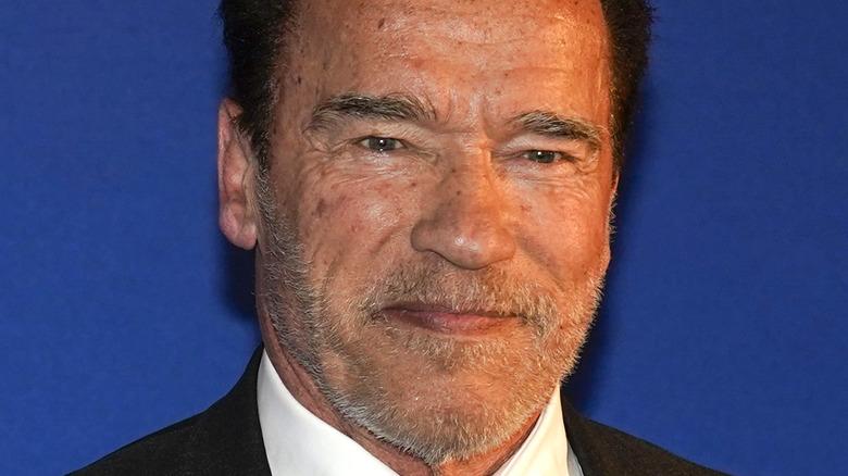 Arnold Schwarzenegger grinning with scruff