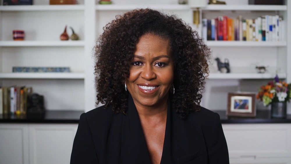 Michelle Obama  in front of her bookshelf