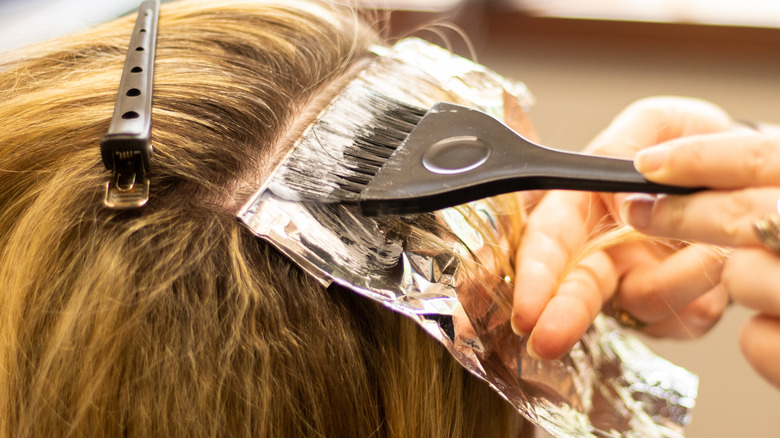 Stylist using foil to create highlights on a clients hair.