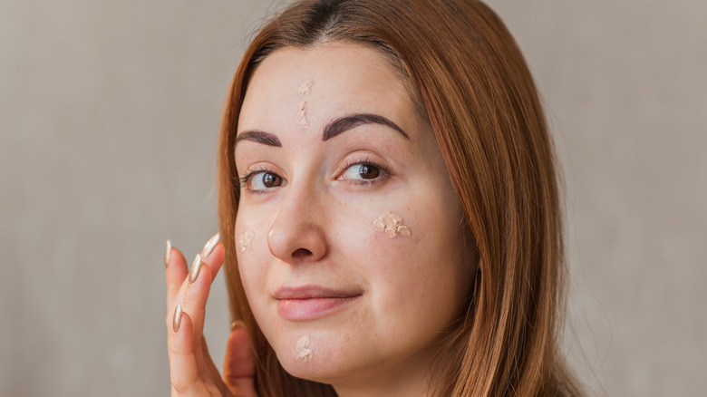 Woman applying concealer to her acne-prone skin.
