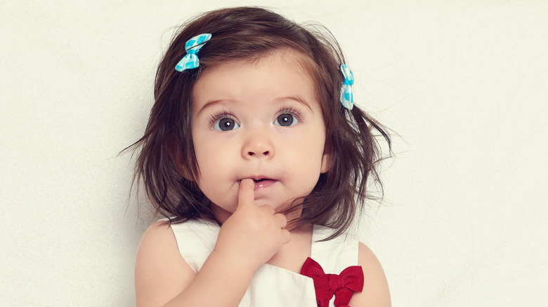 Curious little girl finger in mouth