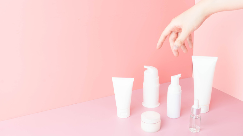Hand reaching out to pick skincare products