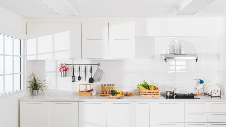 A white, modern kitchen with lots of natural light.