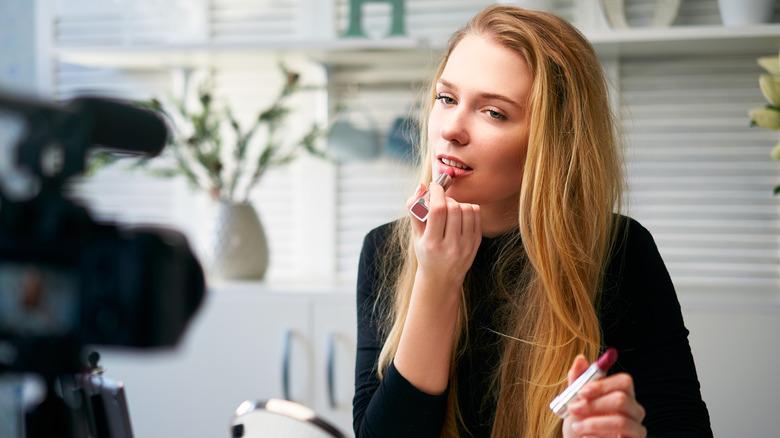 A woman applies lipstick