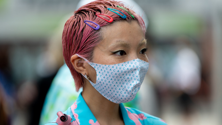 Woman with pink hair wearing mask