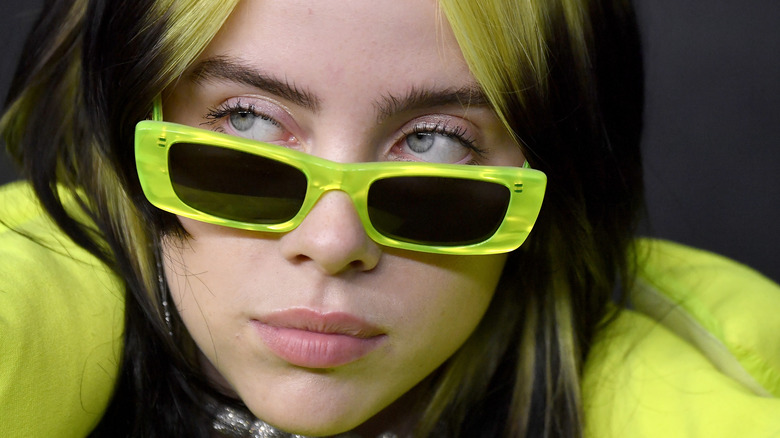 Billie Eilish looking serious with neon green hair and glasses