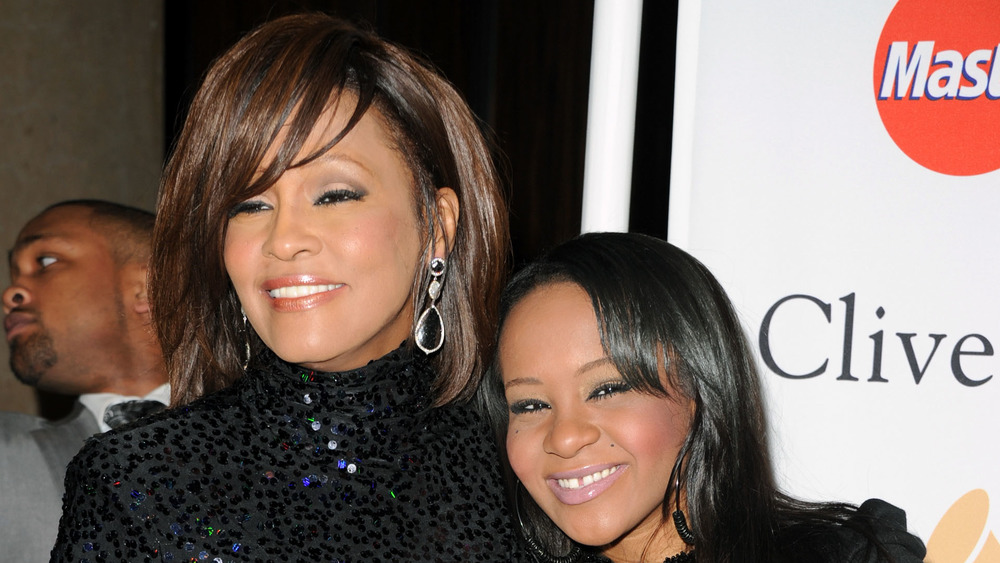 Bobbi Kristina Brown and her mother Whitney Houston smile at an event together
