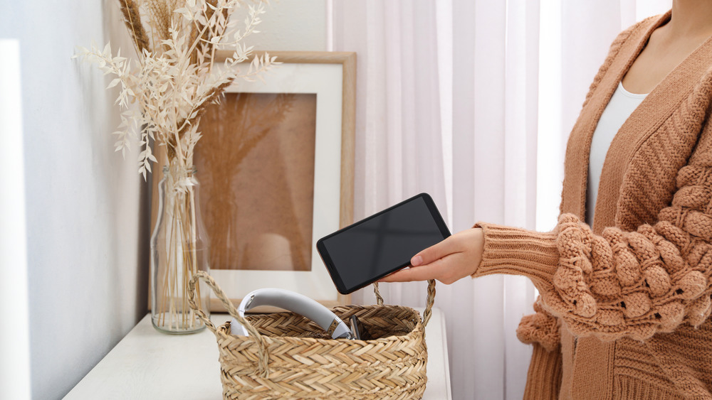 Woman putting phone in a basket
