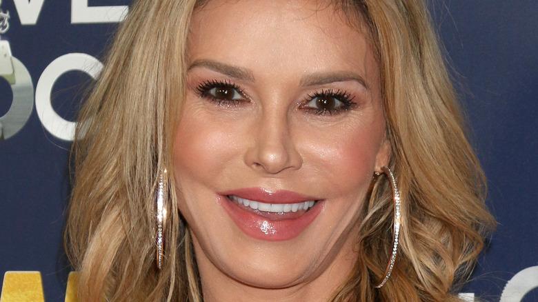 Brandi Glanville smiling with large hoop earrings