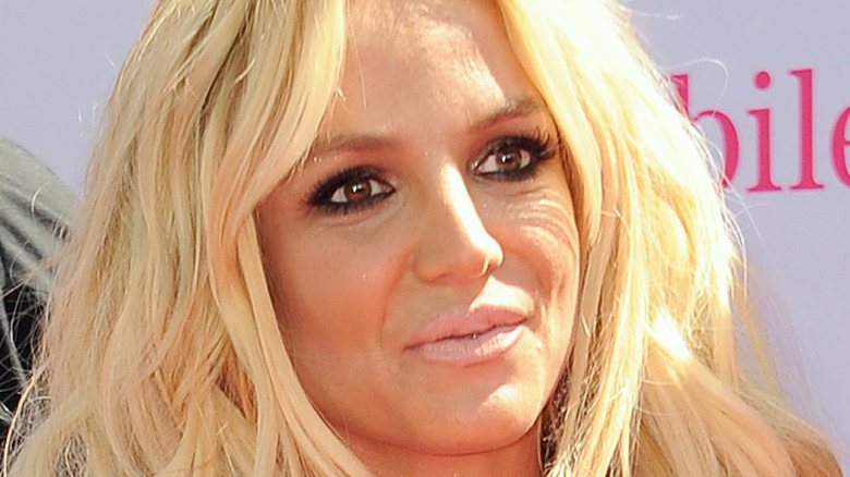 Britney Spears wears a black dress on the red carpet.