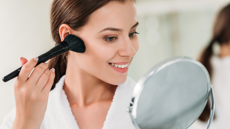 Woman adding bronzer to her face
