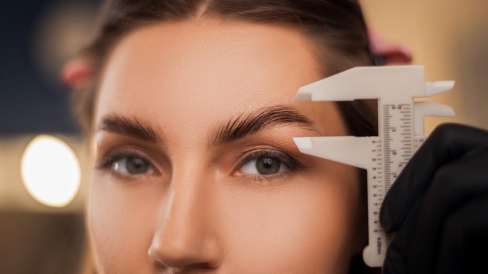 Woman measuring her eyebrows