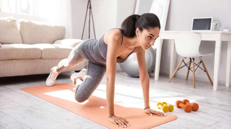 woman working out at home calisthenics weight training