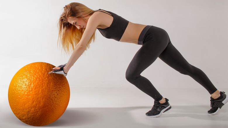 woman pushing orange