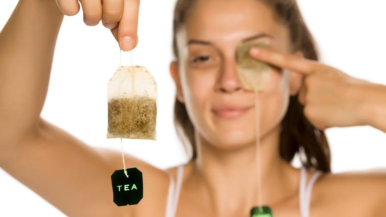 Woman places tea on eye