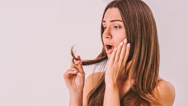 woman surprised at damaged hair