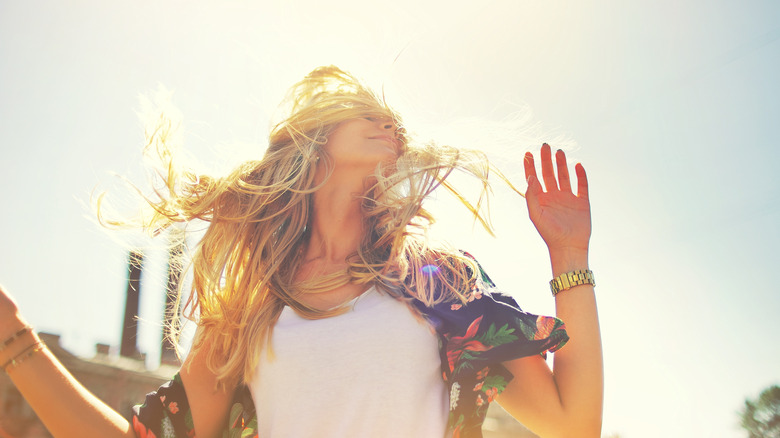 woman smiling with long blonde hair blowing in the wind