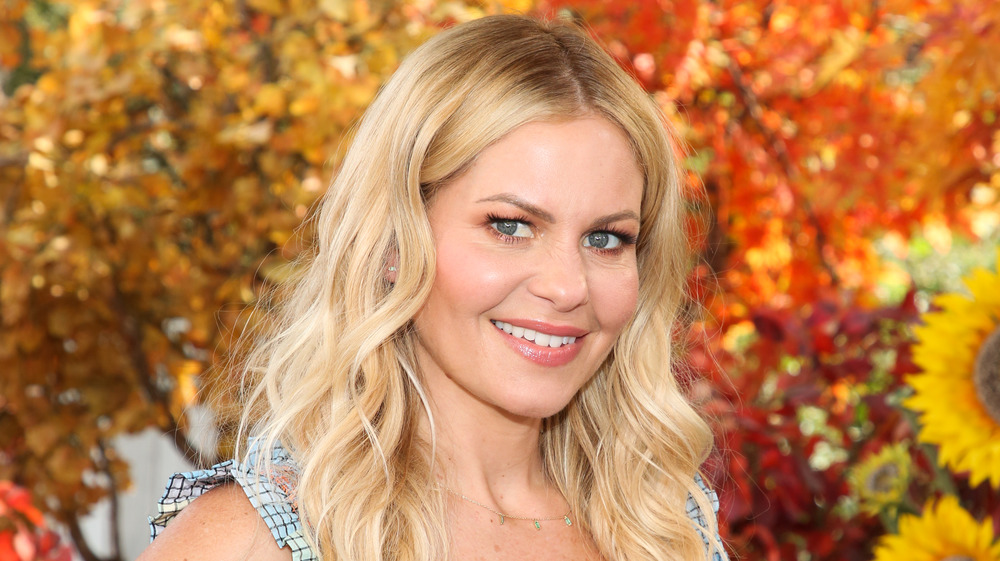 Candace Cameron Bure in front of fall set