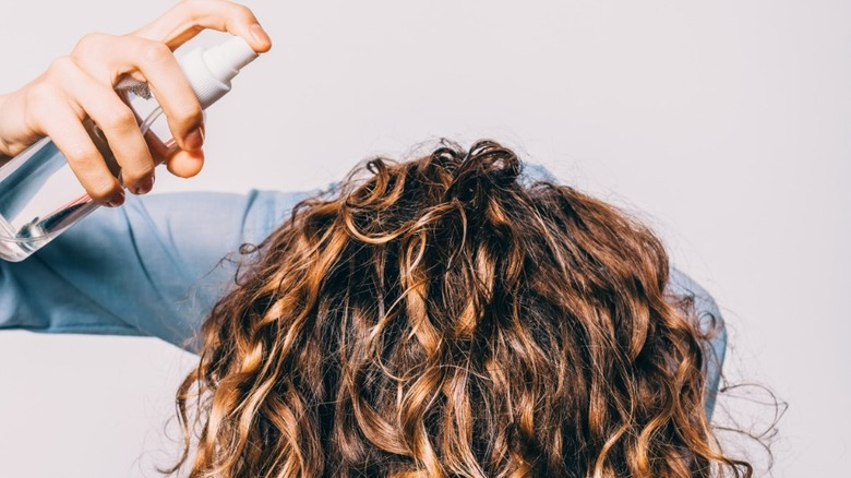Woman with curly hair applying product to her curls