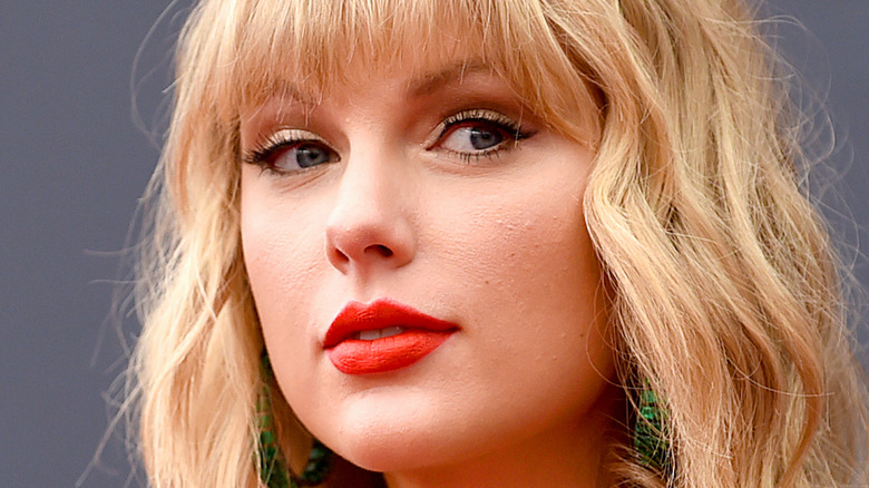 Taylor Swift looking to the side with bright lipstick