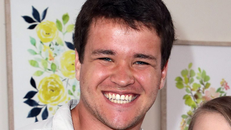 Chandler Powell smiling in white