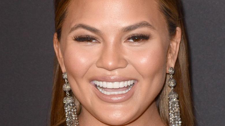 Chrissy Teigen smiling with long earrings