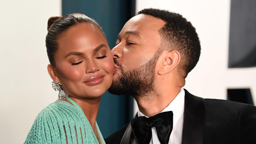 Chrissy Teigen eyes closed getting kiss on the cheek from John Legend